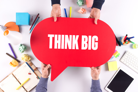 overachieving: Two people holding speech bubble with THINK BIG concept