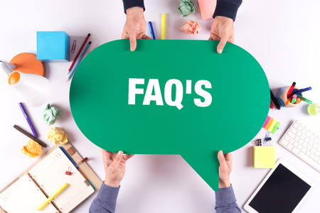 faq's: Two people holding speech bubble with FAQS concept