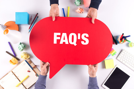 faqs: Two people holding speech bubble with FAQS concept