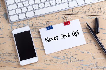 Paper note with text Never Give Up! Stock Photo