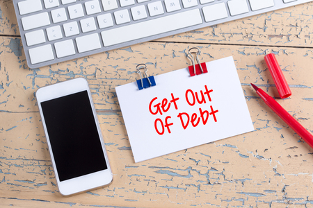 Paper note with text Get Out Of Debt Stock Photo