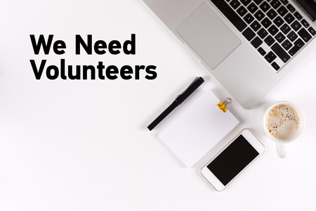 in need of space: We Need Volunteers text on the desk with copy space