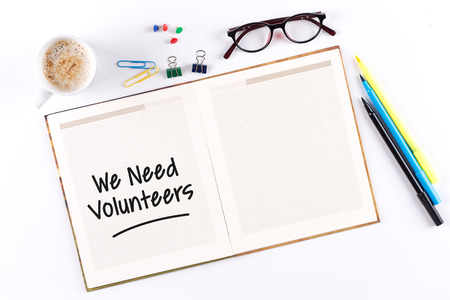 in need of space: We Need Volunteers text on notebook with copy space