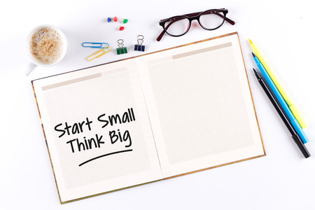 surpass: Start Small Think Big text on notebook with copy space