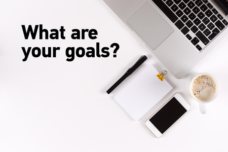 accomplishing: What are your goals? text on the desk with copy space