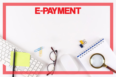epayment: High Angle View of Various Office Supplies on Desk with a word E-PAYMENT