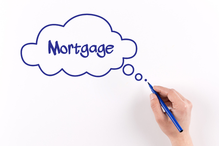 lend a hand: Hand writing Mortgage on white paper, View from above Stock Photo