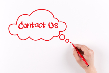 criticize: Hand writing Contact Us on white paper, View from above Stock Photo