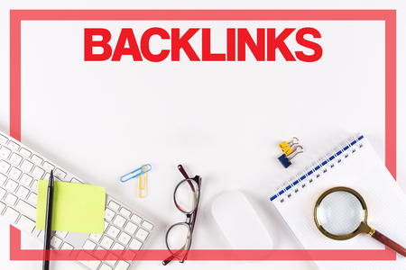 linkbuilding: High Angle View of Various Office Supplies on Desk with a word BACKLINKS