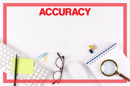 accuracy: High Angle View of Various Office Supplies on Desk with a word ACCURACY Stock Photo