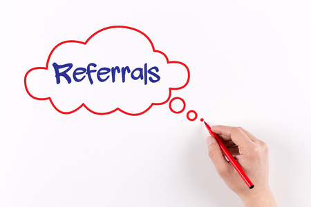 referrals: Hand writing Referrals on white paper, View from above