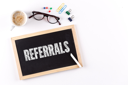 referidos: REFERRALS word on chalkboard with coffee cup, view from above Foto de archivo