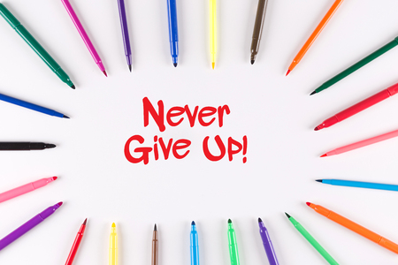 commitment committed: Multi Colored Pen written Never Give Up! phrase Stock Photo