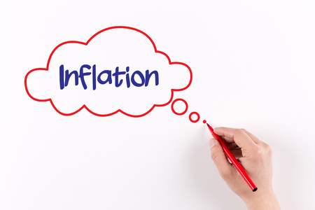 price uncertainty: Hand writing Inflation on white paper, view from above