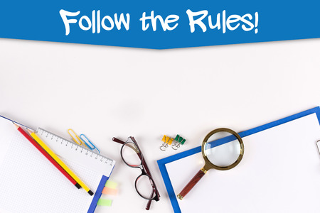 leading education: High Angle View of Various Office Supplies on Desk with a word Follow The Rules!