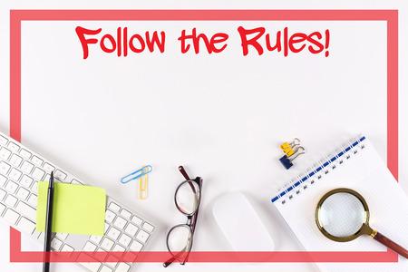 High Angle View de diverses fournitures de bureau sur le bureau avec un mot Suivez les règles!