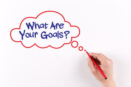 accomplishing: What are Your Goals? phrase on white paper, View from above
