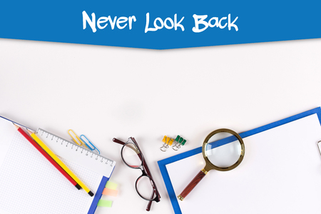 forthcoming: High Angle View of Various Office Supplies on Desk with a phrase Never Look Back