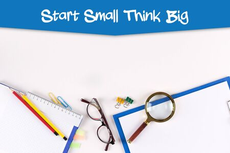 High Angle View of Various Office Supplies on Desk with a word Start Small Think Big Stock Photo