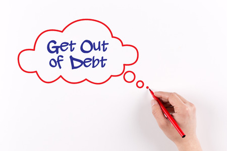 trouble free: Hand writing Get Out of Debt on white paper, View from above