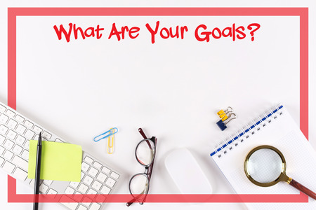 accomplishing: High Angle View of Various Office Supplies on Desk with a phrase What are Your Goals?