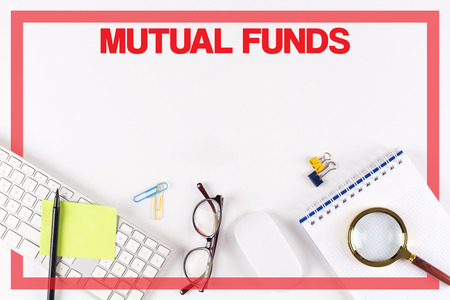 mutual funds: High Angle View of Various Office Supplies on Desk with a word MUTUAL FUNDS