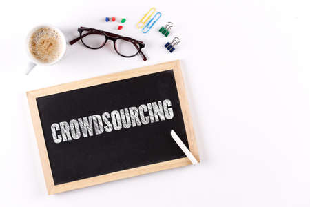 CROWDSOURCING word on Chalkboard with Coffee Cup, view from above Stock Photo