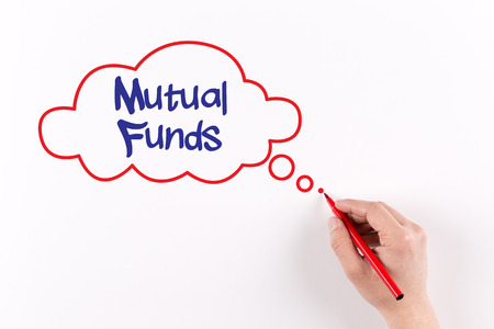 mutual funds: Hand writing Mutual Funds on white paper, View from above Stock Photo
