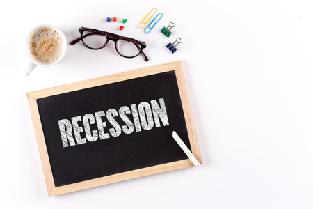 recession: RECESSION word on Chalkboard with Coffee Cup, view from above Stock Photo