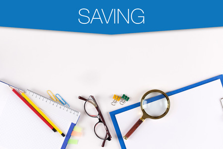 frugality: High Angle View of Various Office Supplies on Desk with a word SAVING