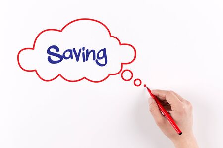 frugality: Hand writing Saving on white paper, view from above Stock Photo