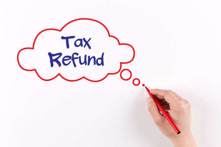 tax refund: Hand writing TAX REFUND on white paper, View from above Stock Photo