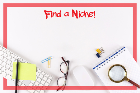 specialize: High Angle View of Various Office Supplies on Desk with a phrase Find a Niche!