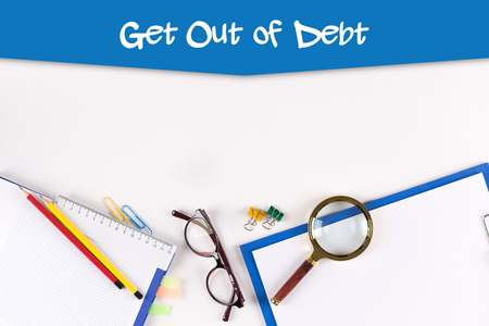 High Angle View of Various Office Supplies on Desk with a word Get Out of Debt Stock Photo