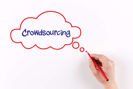 crowd source: Hand writing Crowdsourcing on white paper, View from above Stock Photo