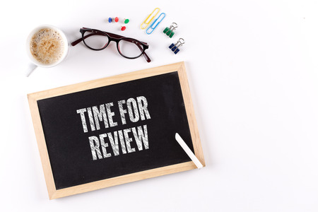 reassessment: TIME FOR REVIEW phrase on chalkboard with coffee cup and eyeglasses, view from above Stock Photo