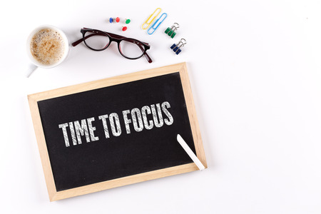distinctness: TIME TO FOCUS phrase on chalkboard with coffee cup and eyeglasses, view from above