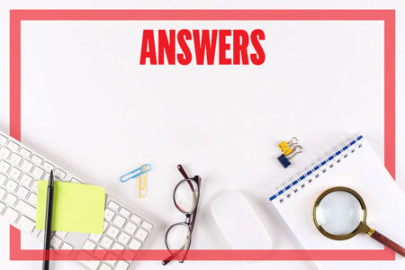 warranty questions: High angle view of various office supplies on desk with a word ANSWERS