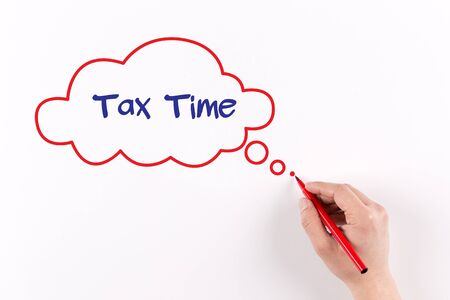 rate of return: Hand writing Tax Time on white paper, view from above Stock Photo