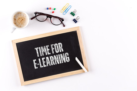 TIME FOR E-LEARNING phrase on chalkboard with coffee cup and eyeglasses, view from above