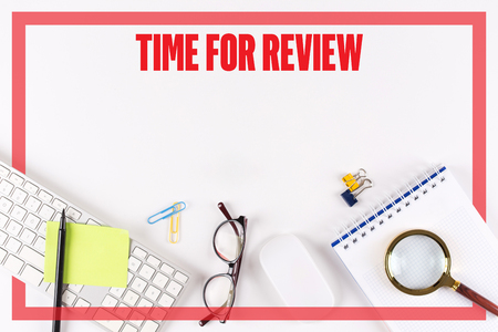 reassessment: High angle view of various office supplies on desk with a word TIME FOR REVIEW