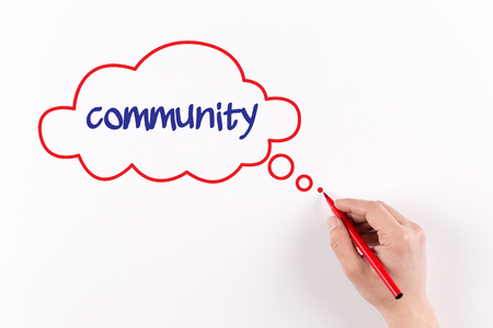 altogether: Hand writing Community on white paper, view from above