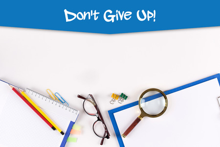 not give: High Angle View of Various Office Supplies on Desk with a phrase Dont Give Up!