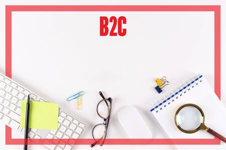 b2c: High angle view of various office supplies on desk with a word B2C