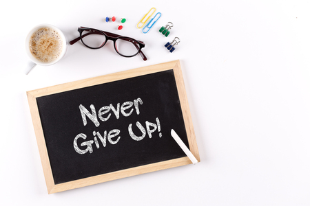 not give: Never Give Up! phrase on Chalkboard with Coffee Cup, view from above