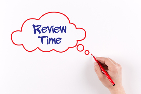 reassessment: Hand writing Review Time on white paper, view from above