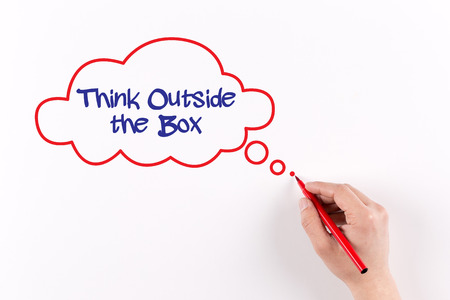 expressing artistic vision: Hand writing THINK OUTSIDE THE BOX on white paper, view from above