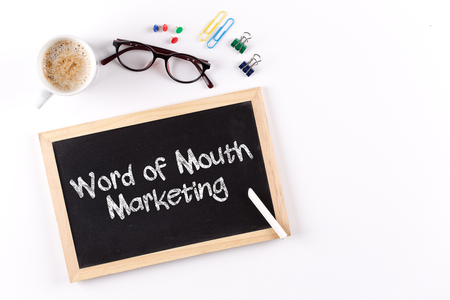referrer: Word of Mouth Marketing word on chalkboard with coffee cup and eyeglasses, view from above Stock Photo