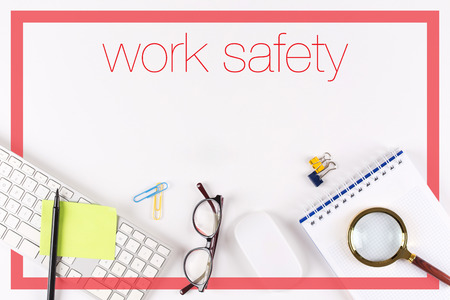 High angle view of various office supplies on desk with a word Work Safety