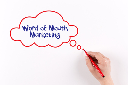 referrer: Hand writing Word of Mouth Marketing on white paper, view from above Stock Photo